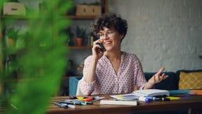 Recht junge Frau ist Gläser spricht auf Handy und lächelndem zu Hause sitzen am Schreibtisch mit Briefpapier stock video footage