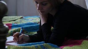 Recht junge Frau liegt auf seinem Magen, der ihre Knie verbiegt und schreibt in ihr Tagebuch jugendliche Erfahrungen Langsame Bew stock video footage