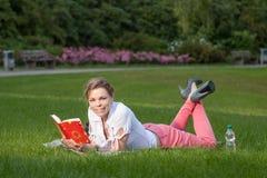Recht junge Frau liest ein Buch Lizenzfreie Stockfotos