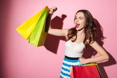 Recht junge Frau mit buntem Einkaufstaschecelebratign und -c$blinzeln Lizenzfreies Stockbild