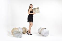 Recht junge Frau mit goldenem Präsentkarton und Dekorationen lächelt Stockfoto