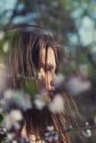 Recht junge Frau nahe Baum mit Blumen Stockfoto