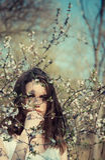 Recht junge Frau nahe Baum mit Blumen Stockfotos