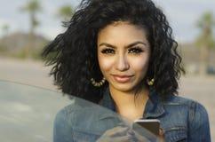 Recht junge Frau neben ihrem Auto, das Telefonanruf macht Stockfotos