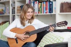 Recht junge Frau spielt Gitarre Stockfotos