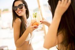 Recht junge Frauen mit coctails auf dem Strand Stockfoto