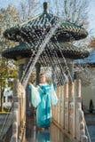 Recht junge Geisha im Wasser fällt in das blaue Kleid, das nahen Brunnen steht Stockbild