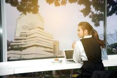 Recht junge Geschäft Asiatin bearbeitet einen Laptop, der in einem Gebäude sitzt Lizenzfreie Stockbilder