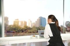 Recht junge Geschäft Asiatin bearbeitet einen Laptop, der in einem Gebäude sitzt Lizenzfreies Stockfoto