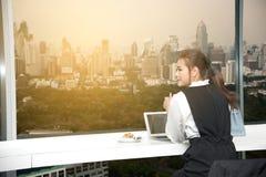 Recht junge Geschäft Asiatin bearbeitet einen Laptop, der in einem Gebäude sitzt Stockfotos