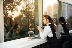 Recht junge Geschäft Asiatin bearbeitet einen Laptop, der in einem Gebäude sitzt Stockbild