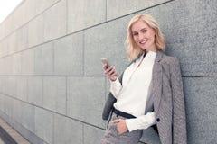 Recht junge Geschäftsfrau benutzt ein Telefon Stockbilder