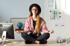 Recht junge Geschäftsfrau, die auf dem Tisch Yoga im Büro tut Lizenzfreie Stockfotografie