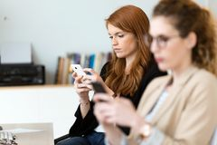 Recht junge Geschäftsfrau, die ihren Handy im Büro verwendet stockfoto