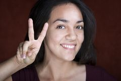 Recht junge hispanische Frau, die Friedenszeichen bildet Stockfoto