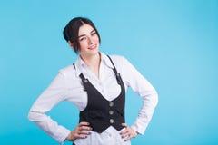 Recht junge lächelnde Brunettefrau in der Weste, die Kamera auf blauem Hintergrund betrachtet stockbilder