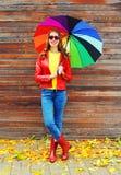 Recht junge lächelnde Frau mit dem bunten Regenschirm, der eine rote Lederjacke und Gummistiefel im Herbst über hölzernem Hinterg lizenzfreie stockfotos