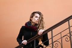 Recht junge Modefrau mit dem langen gelockten Haar, das den Abstand und die Aufstellung im Freien nahe der Wand im Straße backgro Lizenzfreie Stockbilder