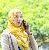 Recht junge moslemische Frau, die ein Gespräch am Telefon hat Lizenzfreie Stockfotos