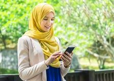 Recht junge moslemische Frauenmitteilung unter Verwendung des Smartphone Stockfoto