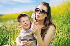 Recht junge Mutter, die Löwenzahn mit Sohn spielt Stockbild
