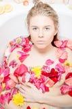 Schöne blonde Dame, die ein Bad mit den Blumenblumenblättern nimmt Stockfotografie