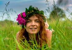 Recht junge sexy Waldnymphe, die in das Gras legt Stockfoto