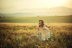 Recht junge smilling Frau mit Retro- Fahrrad im Sonnenuntergang auf der Straße, alte Zeiten der Weinlese, Mädchen im Retrostil au stockfoto