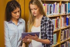 Recht junge Studenten, die zusammen mit Tablette arbeiten stockfoto