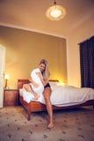 Recht junge verliebte Frau, die auf dem Bett und den Spielen mit einem Kissen sitzt Stockfoto