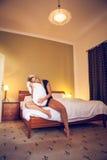 Recht junge verliebte Frau, die auf dem Bett und den Spielen mit einem Kissen sitzt Stockfotos