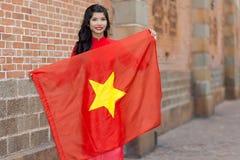 Recht junge vietnamesische Frau, die eine Flagge hält Lizenzfreie Stockbilder