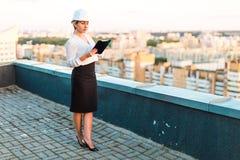 Recht junge Vorarbeiterin im Sturzhelmstand auf dem Dach mit Tablette I Lizenzfreies Stockfoto