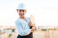Recht junge Vorarbeiterin im Sturzhelmstand auf dem Dach mit Tablette I Stockbild