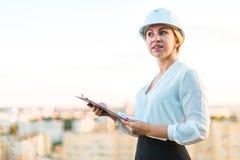 Recht junge Vorarbeiterin im Sturzhelmstand auf dem Dach mit Tablette I Stockfoto