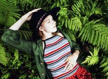 Recht junger blonder Mädchenhippie im Hut unter Farn, Ferien im grünen Wald, Lebensstilmode-Leutekonzept Stockfotografie