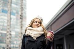 Recht junger blonder trinkender Kaffee draußen an einem bewölkten Tag Lizenzfreie Stockbilder