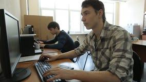 Recht junger Mann arbeitet an Computer im Büro in der Tageszeit stock footage