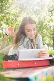 Recht junger Student, der auf dem Gras studiert mit ihrem Tabletten-PC liegt Stockfotografie