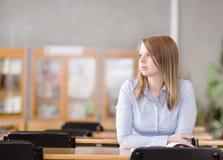 Recht junger Student in einer Bibliothek Weg schauen Stockbild