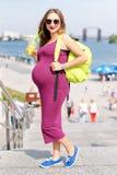 Recht junger trinkender Saft der schwangeren Frau und Genießen sie gehend auf den Stadtdamm Frauentourist, Active und Stockfoto