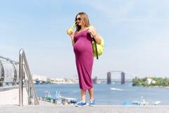 Recht junger trinkender Saft der schwangeren Frau und Genießen sie gehend auf den Stadtdamm Frauentourist, Active und Lizenzfreie Stockfotos