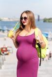 Recht junger trinkender Saft der schwangeren Frau und Genießen sie gehend auf den Stadtdamm Frauentourist, Active und Stockfotografie