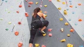 Recht junges athletisches Mädchen, das auf einer Innenkletternwand klettert stock footage