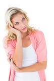 Recht junges blondes Denken mit der Hand auf Kopf Stockbild