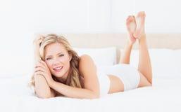 Recht junges blondes Lügen auf ihrem Bett, das Kamera betrachtet Stockfotografie