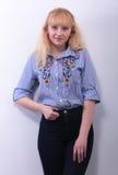 Recht junges blondes Mädchen auf Grau Stockfoto