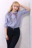 Recht junges blondes Mädchen auf Grau Lizenzfreie Stockfotografie
