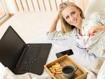 Recht junges blondes Mädchen, das an einem Laptop sitzt auf dem Bett arbeitet Schöne junge Frau in einer flaumigen weißen Strickj Lizenzfreie Stockfotos