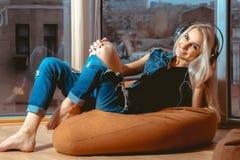 Recht junges blondes Mädchen, hörend Musik in den Kopfhörern Lizenzfreie Stockfotos